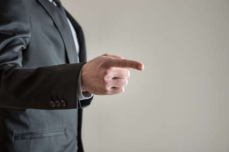 Businessman pointing his finger towards a blank grey space on the right side of an image.