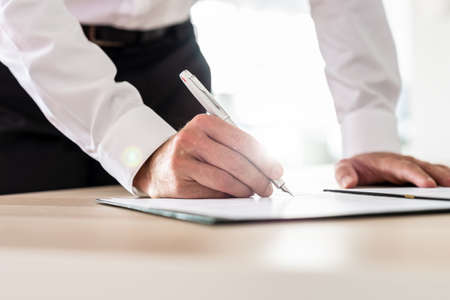 Business executive signing a contract with ink pen with bright sunlight in background.