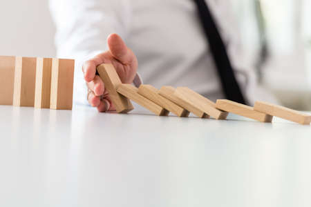 Business intervention concept - businessman putting a stop to a collapsing dominos with his hand.
