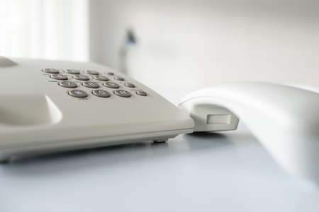 Closeup of white landline telephone with handset off the hook on desk in a bright office.