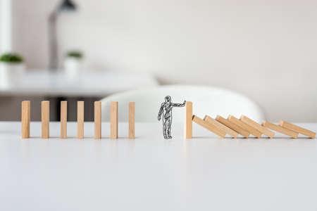 Forme dessinée à la main d'un homme d'affaires arrêtant l'effet domino dans une image conceptuelle de la résolution de la crise commerciale.
