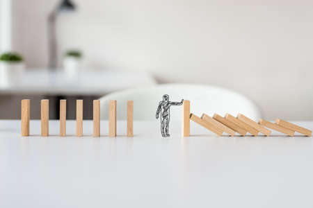 Hand drawn shape of businessman stopping domino effect in a conceptual image of solving business crisis. 免版税图像