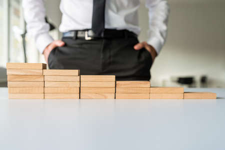 Staircase made of wooden pegs on office desk with business executive standing next to it in a conceptual image. Imagens