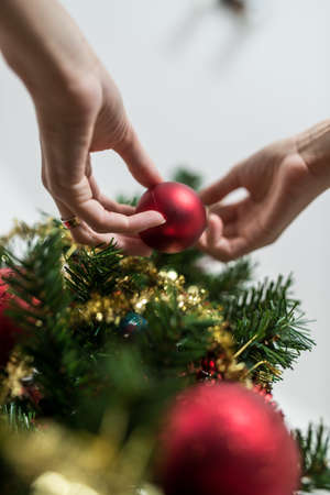 View from below of female hand placing red holiday bauble on Christmas tree.