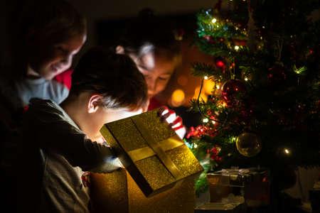 Trois enfants, deux tout-petits garçons et une fille, ouvrant une boîte-cadeau dorée avec de la lumière qui en sort sous un sapin de Noël avec des lumières de Noël. Banque d'images