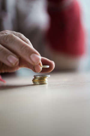Closeup of male senior hand counting Euro coins by stacking them in a conceptual image. Stock Photo