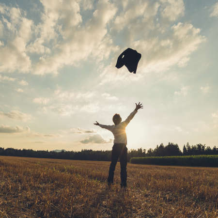 Successful businessman celebrating his achievement standing in nature throwing his suit jacket high up in the air. Stock Photo