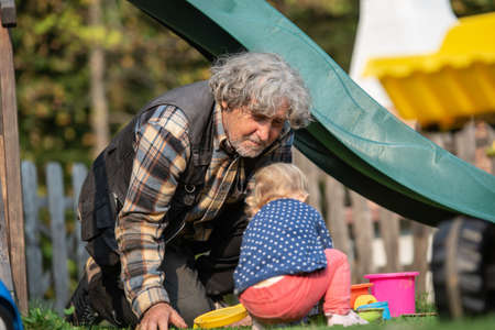 Grandpa playing with his granddaughter outside in playground