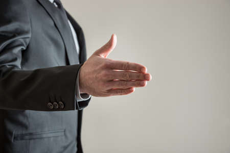 Businessman standing to the left side of the image offering his hand in handshake over grey background. With copy space. Фото со стока