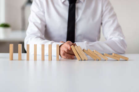 Front view of business executive sitting at his office desk stopping domino effect with the palm of his hand in a conceptual image.