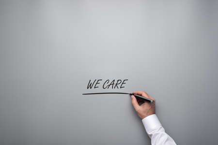 Male hand underlining a we care sign with black marker written over grey background. Stock Photo