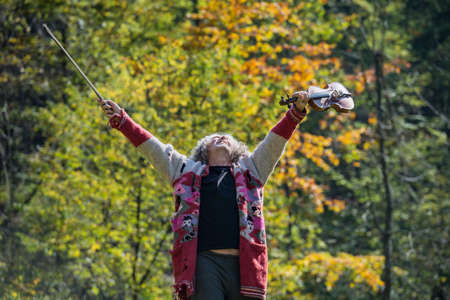 Senior homeless man with torn old sweater celebrating life lifting his violin and bow high up in the air outside with trees in background.