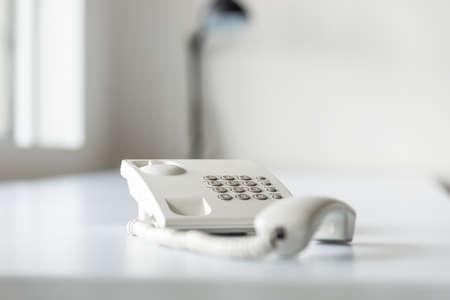 White landline telephone with handset off line on white office desk. Stock Photo