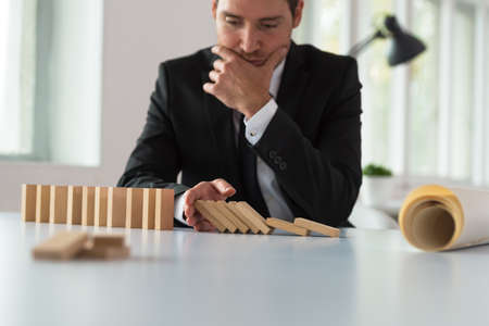 Worried serious businessman sitting at his desk stopping domino effect with his hand as he plans the future of his company.