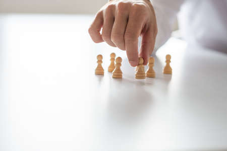 Closeup of businessman hand arranging peasant chess pieces on white office desk in a conceptual image of leadership and human resources. Banco de Imagens - 115501035