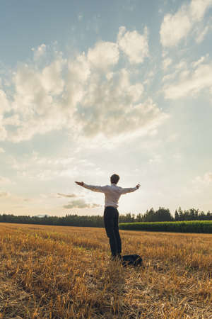 Young businessman standing in the middle of a sawn field under beautiful sky with his arms spread widely. Foto de archivo - 115501069