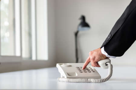 Businessman hand dialing a telephone number using white landline phone on white office desk.