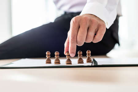 Business leader sitting on his desk making human resources decisions by positioning pawn chess pieces on paperwork. 스톡 콘텐츠