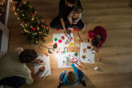 Top view of family of five sitting on wooden living room floor next to a Christmas tree having fund making holiday ornaments, drawing and painting. Imagens