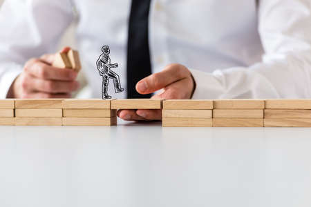 Business teamwork and collaboration concept - silhouette of a businessman walking across a bridge made of wooden pegs supported by male hand. Stock Photo - 115203075