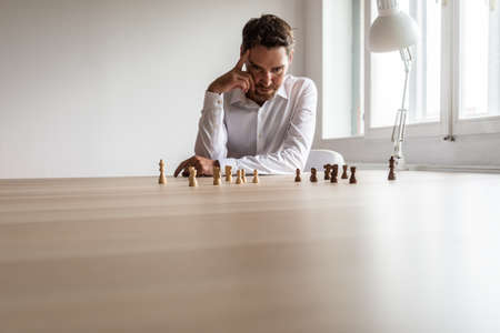 Young business executive leader siting at his desk with teams of black and white chess pieces on hiss office desk making hr decisions.