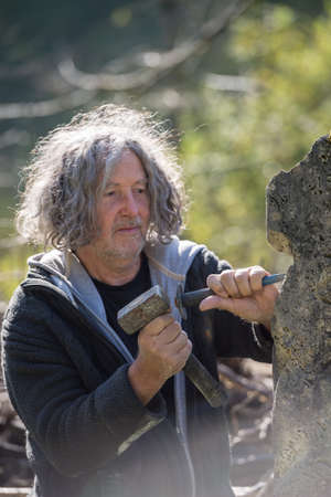 Senior bohemian sculptor with long curly hair carving stone outside in daylight.