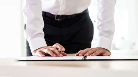 Business employer signing an application form or other important document standing behind his desk.