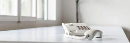 Wide view image of white landline telephone with handset off line on office desk with bright windows in background. Stock Photo