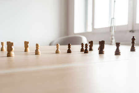 Black and white chess pieces teamed up and facing each other on a wooden office desk in a conceptual image of business competition.