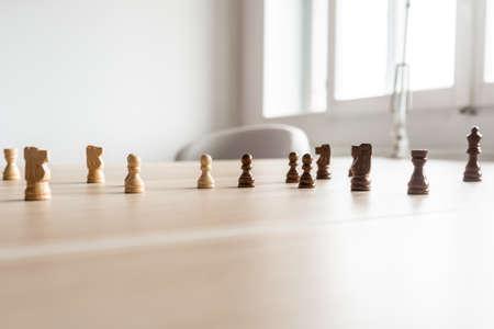 Pezzi degli scacchi in bianco e nero uniti e uno di fronte all'altro su una scrivania in legno in un'immagine concettuale della concorrenza tra imprese. Archivio Fotografico