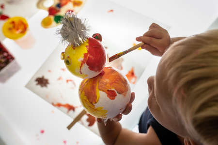 Overhead view of toddler boy making holiday decoration colouring a snowman Stock Photo