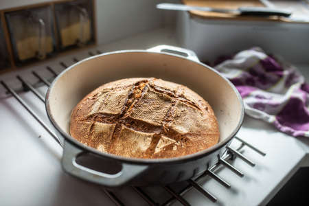 Freshly baked homemade bread in a clay pot cooling on a kitchen counter.