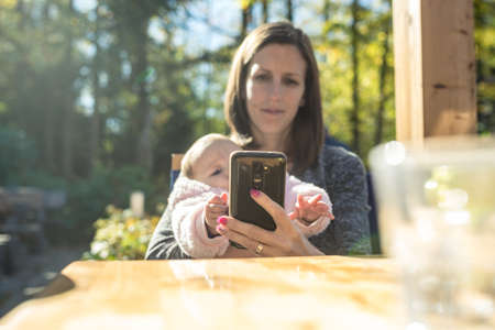 Young mother using her mobile phone as she is sitting outside in a coffee holding her baby daughter reaching for the phone. Stock Photo