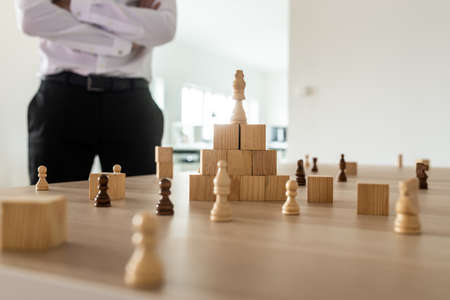 Business executive standing by his office desk working on company strategy - wooden cubes and chess pieces positioned in pyramid shape and placed around it on the table. Reklamní fotografie