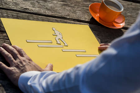 Business vision and success strategy concept - businessman looking at a piece of yellow paper with paper cut businessman climbing up the stairs towards his ambition.