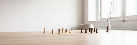 Wide view image of black and white chess pieces placed on wooden office desk facing each other in a conceptual image. Stock Photo