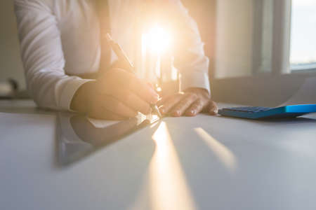 Low angle view of an architect or engineer sitting at his office desk drawing with pencil using a ruler with bright sun flare coming from the window in background.
