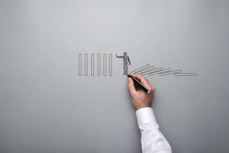 Male hand drawing shape of a businessman stopping domino effect over grey background in a conceptual image. With copy space. Stockfoto