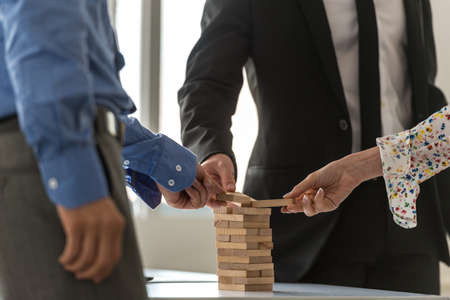 Business team of three businesspeople working together to build a tower of wooden pegs in a conceptual image. Stock Photo - 115558678