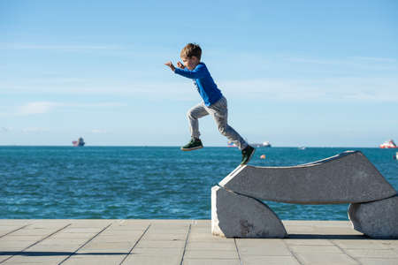 Toddler boy jumping from a stone sculpture by the sea on a sunny autumn day. Stock Photo
