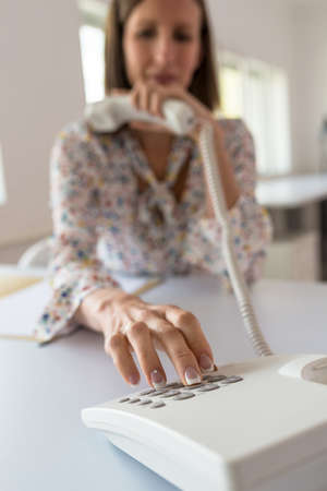 Young secretary sitting at her office desk dialing a telephone number holding handset of white landline phone. Focus to her fingers and keypad.