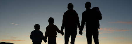 Silhouette of a family of five standing under the evening sky with their backs to the camera. Stock fotó