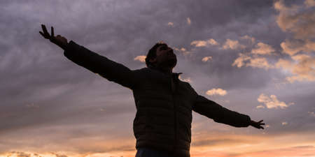 Low angle view of young man standing under glowing evening sky with his arms outstretched celebrating life and freedom.