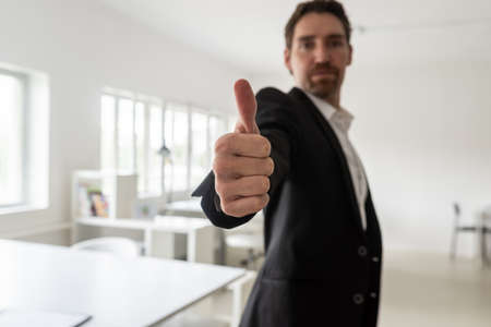 Young businessman standing in his bright office making a thumbs up gesture toward the camera. 스톡 콘텐츠