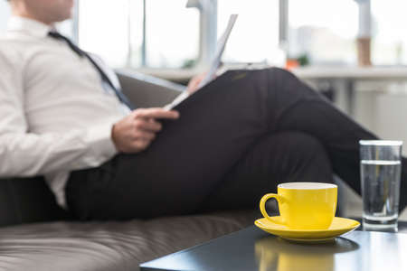Business executive or lawyer sitting on his office couch reading a document with cup of coffee and glass of water on coffee table. Stock Photo