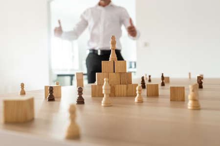 Chess figures and wooden locks positioned on office desk with king on top of a pyramid with businessman in background showing a thumbs up sign.