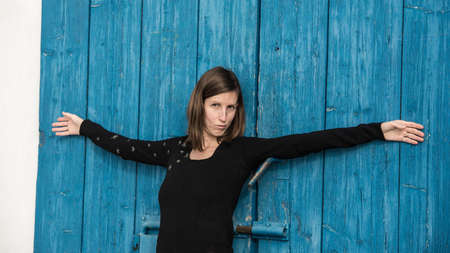 Young woman leaning on blue rustic wooden door with her arms wide open making a funny flirting face towards the camera. Imagens