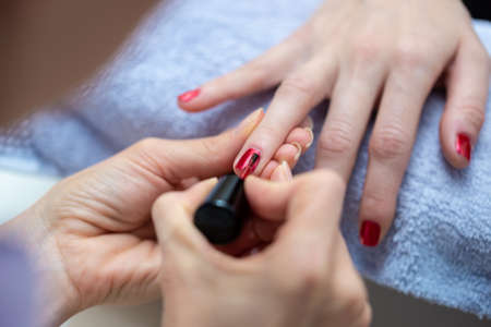 Over the shoulder view of professional manicurist coloring womans nails with shiny red nail polish. 스톡 콘텐츠