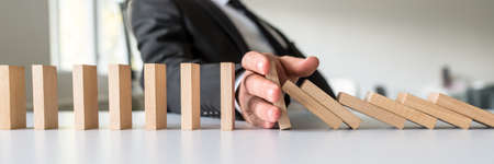 Wide view image of business mediator stopping falling wooden dominos with his hand in a conceptual image of business crisis solution.