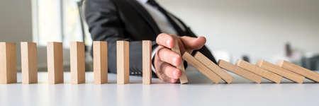 Weitblickbild des Geschäftsmediators, der das Herabfallen von hölzernen Dominosteinen mit seiner Hand in einem konzeptionellen Bild der Lösung für Geschäftskrisen stoppt. Standard-Bild